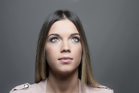 Conceptual portrait of lit young pensive woman with green eyes looking up over gray studio background