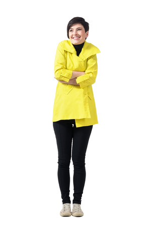 Cold freezing woman wearing yellow coat with crossed arms looking up. Full body length portrait isolated over white studio background.
