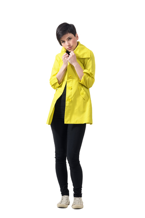 Young short hair brunette freezing covering neck with yellow rain coat. Full body length portrait isolated over white studio background.