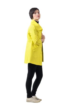 tog: Side view of pretty feminine short hair brunette wearing yellow coat. Full body length portrait isolated over white studio background. Stock Photo