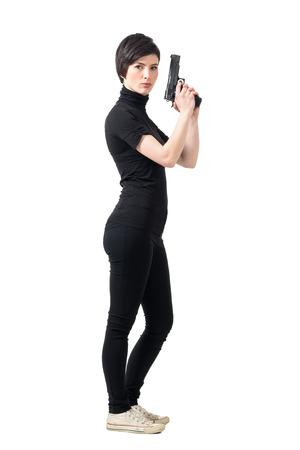 Vista lateral de la mujer dura armado que sostiene el arma que mira a la cámara. la longitud del cuerpo Retrato completo aislado sobre fondo blanco del estudio. Foto de archivo