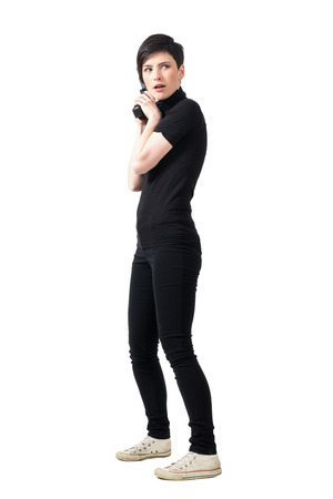 femme fatale: Side view of cautious female spy in black clothes with gun looking behind. Full body length portrait isolated over white studio background.