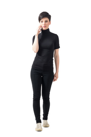 turtleneck: Serious elegant woman in black turtleneck walking and talking on the mobile phone. Full body length portrait isolated over white studio background.