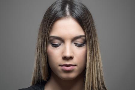 ojos cerrados: temperamental retrato de la belleza con la piel perfecta mirando hacia abajo sobre fondo gris de estudio