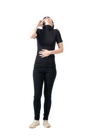 head back: Laughing young woman on the cellphone holding stomach with head back. Full body length portrait isolated over white studio background.
