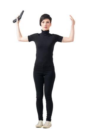 femme fatale: Surrender concept. Scared female spy in black clothes with raised arms holding gun looking at camera. Full body length portrait isolated over white studio background.