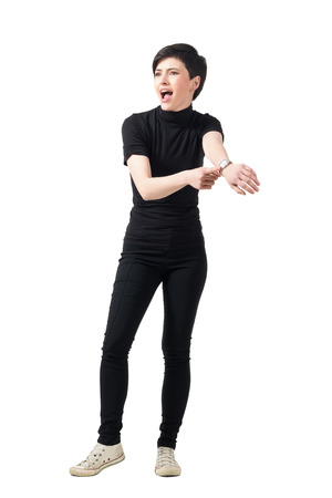 watch over: Angry woman shouting and pointing at wrist watch looking away. Full body length portrait isolated over white studio background. Stock Photo