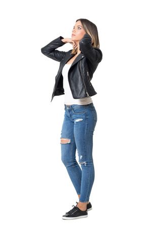 Young beautiful girl in jeans and leather jacket adjusting hair. Full body length portrait isolated over white background Foto de archivo