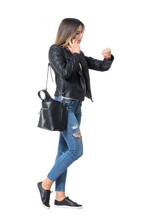caminando: Vista lateral de ocupado chica de moda casual en el teléfono que controla la hora en su reloj. longitud de cuerpo completo retrato aislado sobre fondo blanco Foto de archivo