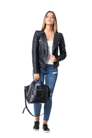 Gorgeous stylish casual woman wearing jeans and leather jacket holding black handbag. Full body length portrait isolated over white background