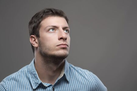 Moody portrait of successful young ceo visionary in blue shirt looking up Stock Photo