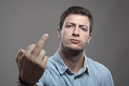 insulting: Dramatic moody portrait of young man showing middle finger gesture at camera Stock Photo