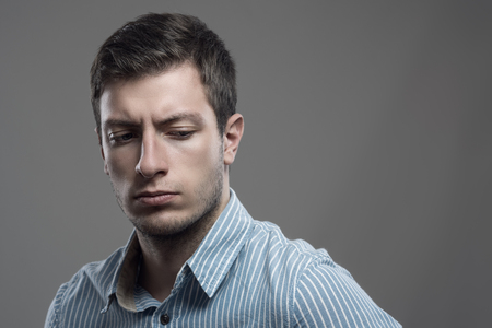 Dramatic intense high contrast portrait of upset young businessman looking back over the shoulder Stock Photo