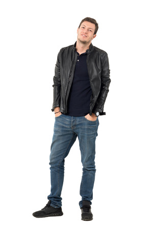 Young casual man in leather jacket and blue jeans with smirk smile tilting head. Full body length portrait isolated over white studio background. Stock Photo