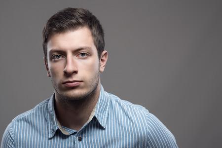 青いシャツを着て copyspace でカメラを見て深刻な若者の不機嫌そうな劇的な肖像