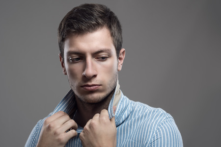 man looking down: Intense moody portrait of young stubble man holding collar looking behind over shoulder