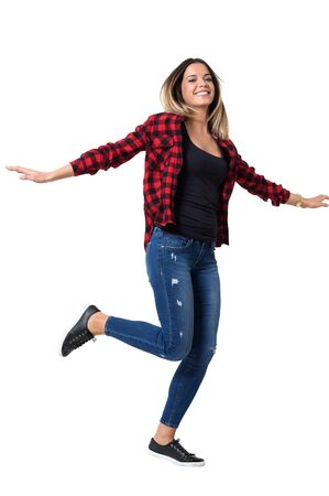 Pretty young woman running with arms spread wearing jeans and red checkered shirt.  Full body length standing portrait isolated over white background.