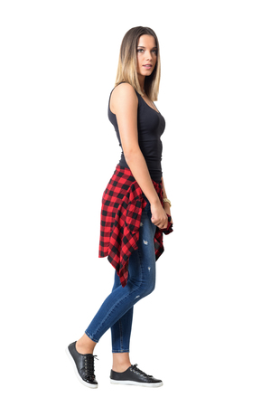 isolated woman: Side view of young serious woman walking with shirt around waist looking at camera.  Full body length standing portrait isolated over white background.