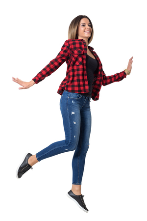 mid air: Carefree young cheerful woman in jeans and red plaid shirt jumping in mid air.  Full body length standing portrait isolated over white background.