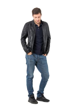 Sad casual man met handen in de zakken op zoek naar beneden. Full body lengte portret over een witte achtergrond. Stockfoto