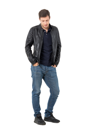 Sad casual man with hands in pockets looking down. Full body length portrait isolated over white background.