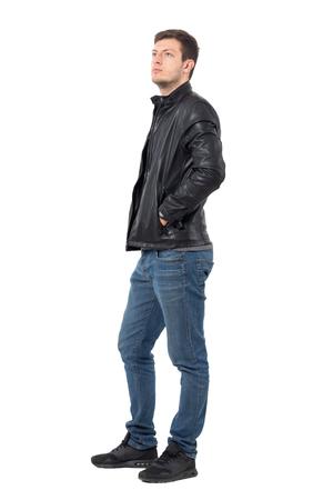 Seitenansicht des jungen beiläufigen Mannes mit den Händen in der Lederjackentaschen Nachschlagen ernst. Ganzkörper-Länge Portrait über weißem Hintergrund. Standard-Bild - 70756018