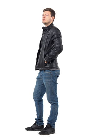 Side view of young casual man with hands in leather jacket pockets looking up serious. Full body length portrait isolated over white background. Stock Photo