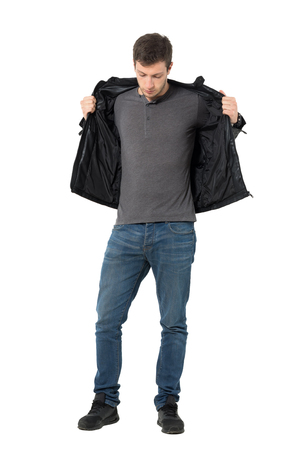 Casual man in jeans taking off leather jacket looking down. Full body length portrait isolated over white background.