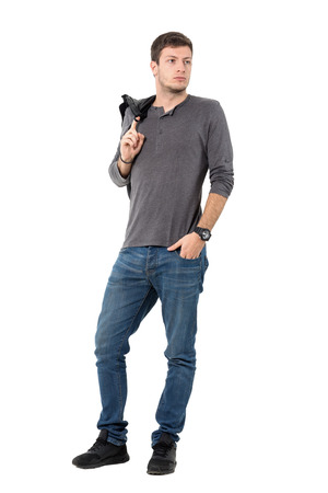 shoulder carrying: Casual handsome young man carrying jacket over shoulder looking away. Full body length portrait isolated over white background.