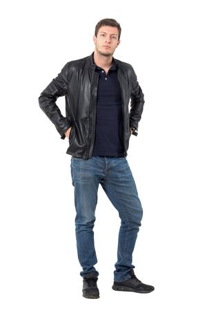 Jonge toevallige man in lederen jas met handen in zakken die naar de camera kijken. Full body lengte portret geïsoleerd over witte achtergrond.