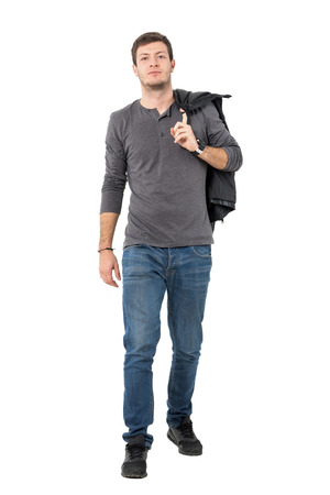 shoulder carrying: Casual young man walking forward carrying jacket over shoulder looking at camera. Full body length portrait isolated over white background.