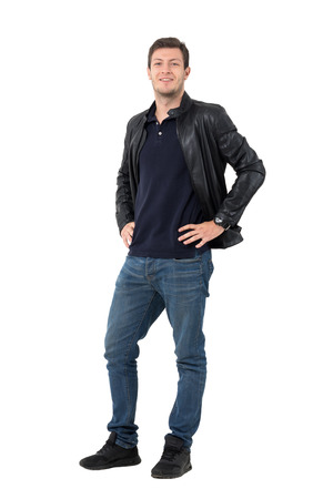 Young casual man with hands on hips smirking and looking at camera. Full body length portrait isolated over white background. Stock Photo