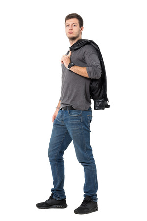 Side view of casual young man carrying jacket over shoulder looking at camera. Full body length portrait isolated over white background.