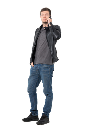 Serious casual young man in jeans and leather jacket talking on the cellphone. Full body length portrait isolated over white background.