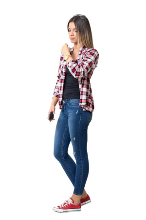 Serious young casual woman walking and adjusting shirt looking down. Full body length portrait isolated over white studio background.