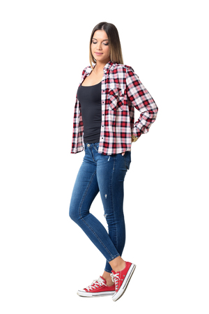 Beautiful shy casual girl wearing jeans, red and white plaid shirt and sneakers looking down. Full body length portrait isolated over white studio background.