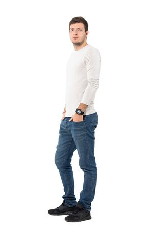 man side: Side view of young serious casual man wearing jeans and sneakers looking at camera. Full body length portrait isolated over white studio background.
