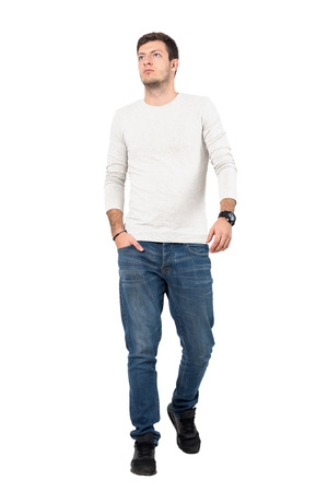 Relaxed young man in casual wear walking towards camera looking up. Full body length portrait isolated over white studio background.