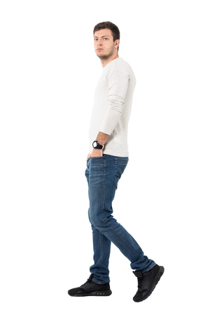 man profile: Side view of casual man in jeans and light gray shirt walking and looking at camera. Full body length portrait isolated over white studio background.