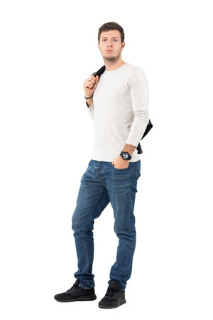 shoulder carrying: Young male fashion model in casual clothes carrying leather jacket over shoulder. Full body length portrait isolated over white studio background. Stock Photo