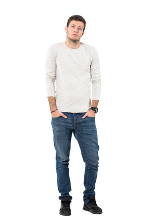 over white: Young casual handsome man wearing jeans and sneakers with hands in pockets. Full body length portrait isolated over white studio background.