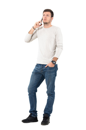 Serious young casual man talking on the mobile phone looking up. Full body length portrait isolated over white studio background.