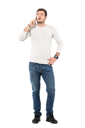 Upset young casual man arguing on the mobile phone. Full body length portrait isolated over white studio background.
