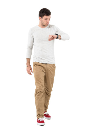 Stylish young man walking and checking time on wrist watch. Full body length portrait isolated over white studio background.