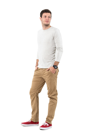 Relaxed young man in beige pants and gray shirt smiling looking back over shoulder. Full body length portrait isolated over white studio background. Stock Photo