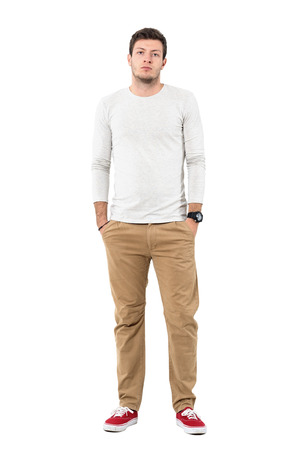 Serious young man in red sneakers and ocher pants with hands in pockets. Full body length portrait isolated over white studio background. Stock Photo
