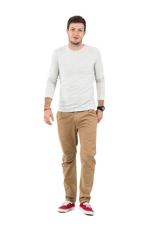 Friendly smiling man in beige pants walking towards camera. Full body length portrait isolated over white studio background.