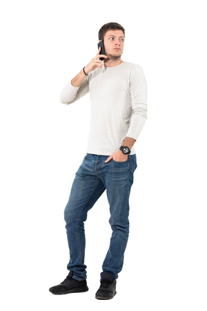 Upset man talking on the phone looking back over the shoulder. Full body length portrait isolated over white studio background.
