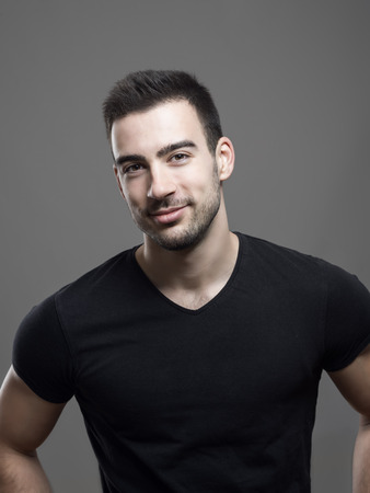 Moody portrait of confident young smiling fitness male model in blank black shirt over gray studio background. Stockfoto
