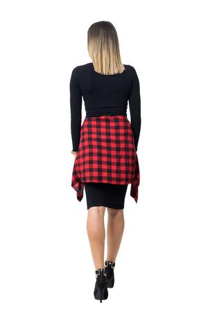 Terug oog van de elegante jonge vrouw in zwarte kleding en stiletto schoenen weglopen. Full body lengte geïsoleerd op een witte achtergrond studio. Stockfoto